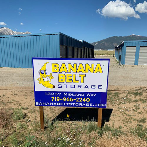 A photograph of self storage units under a blue sky behind a Banana Belt Storage sign