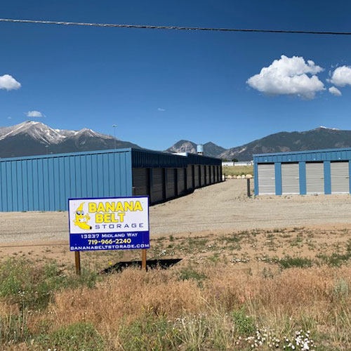 A photograph of several self storage buildings under a blue sky behind a Banana Belt Storage sign