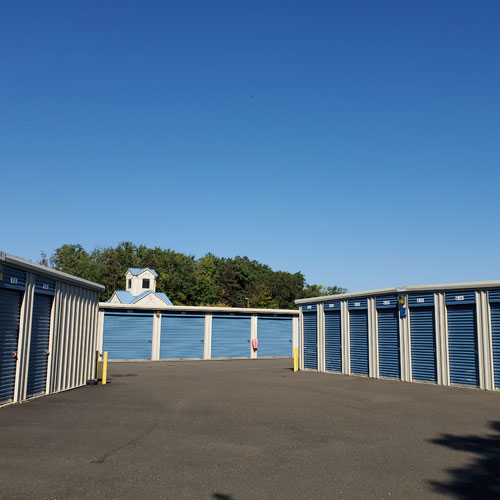 photograph of self storage buildings with blue roll-up doors under a clear sky