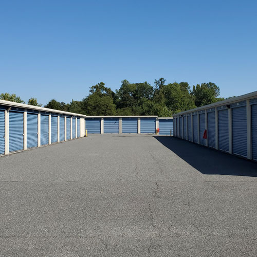 photograph of several self storage buildings with blue roll-up doors under a clear sky