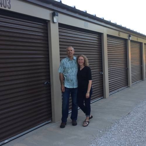 photograph of two people standing in front of self storage units