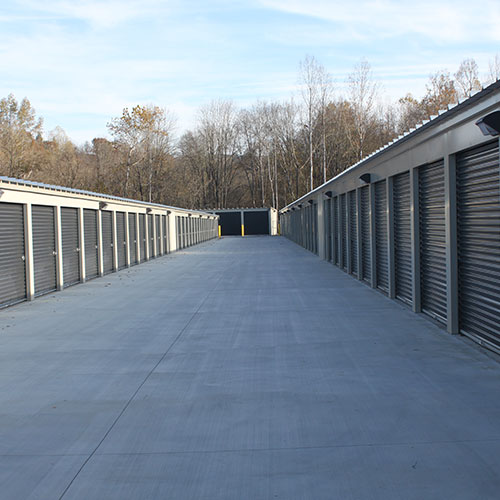 photograph of a concrete drive lined on either side by closed self storage unit doors