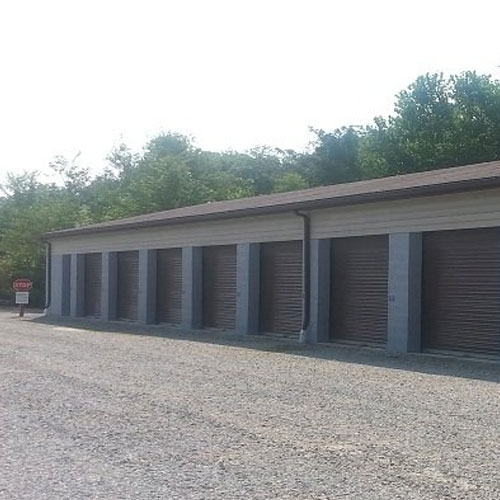A photograph of outdoor self storage units made of concrete blocks with roll up doors