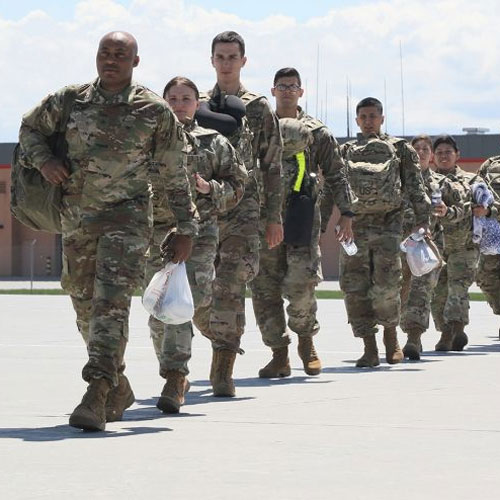 Photograph of soldiers at Fort Drum walking across a tarmac to board a plane